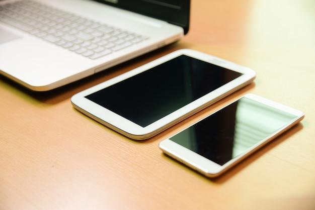 Computer portatile del fuoco molle con taptet e telefono dello smarth sullo scrittorio di legno