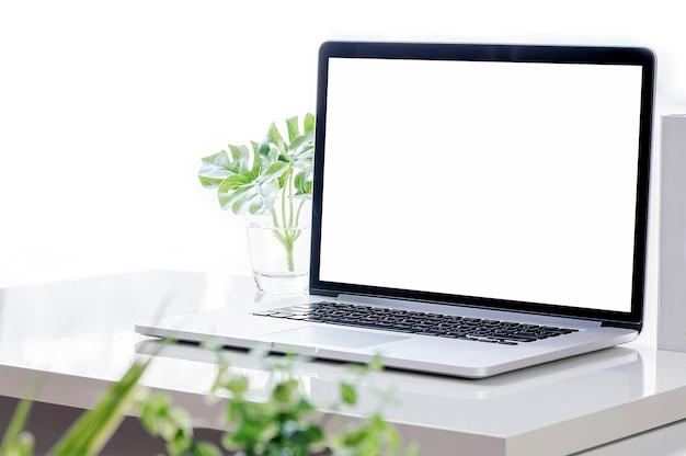 Computer portatile del modello con lo schermo in bianco e la pianta d'appartamento sul tavolo superiore bianco