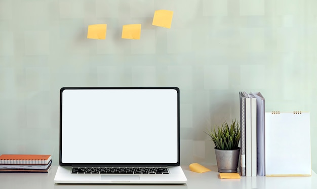Computer portatile del modello con lo schermo in bianco e rifornimenti sul tavolo