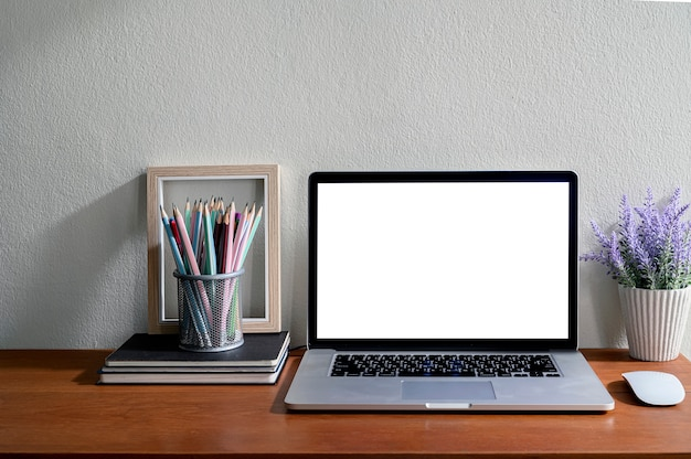 Computer portatile del modello con lo schermo in bianco e rifornimenti sulla tavola di legno.