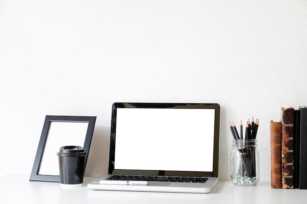 Computer portatile del modello su area di lavoro con la tazza e il libro di caffè.