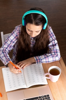 Computer portatile dell'allievo che fa nota, cuffie di musica d'ascolto e libro di lettura, caffè della bevanda. concetto di e-learning.