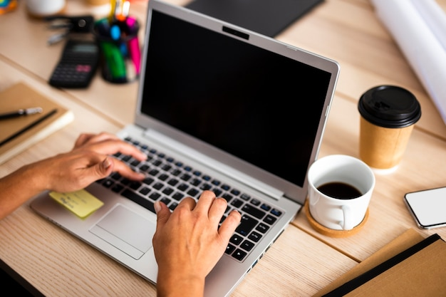 Computer portatile dell'angolo alto sullo scrittorio all'ufficio