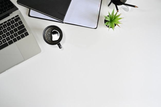 Computer portatile della scrivania di vista superiore, caffè, taccuino con la matita sulla tavola bianca.