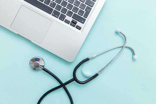 Computer portatile della tastiera dello stetoscopio isolato su fondo blu.