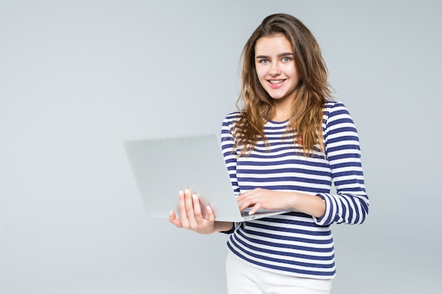 Computer portatile della tenuta della giovane donna su fondo bianco
