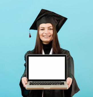 Computer portatile della tenuta della ragazza di vista frontale