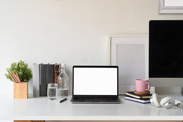 Computer portatile dello schermo in bianco con il manifesto e le forniture per ufficio in bianco.