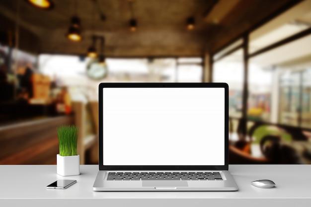 Computer portatile dello schermo in bianco con il topo, il telefono cellulare e il piccolo albero nel ristorante del caffè