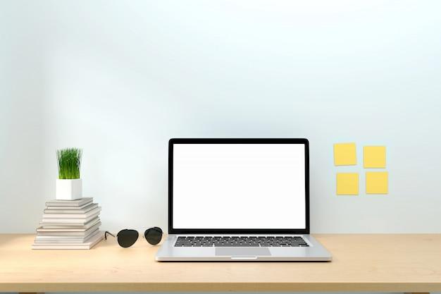 Computer portatile dello schermo in bianco con la nota appiccicosa del libro sullo scrittorio dell'area di lavoro dell'ufficio