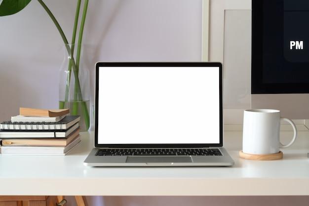 Computer portatile dello schermo in bianco del modello su spazio di lavoro bianco