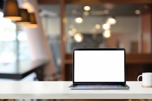 Computer portatile dello schermo in bianco del modello sulla tavola bianca dello scrittorio in ufficio
