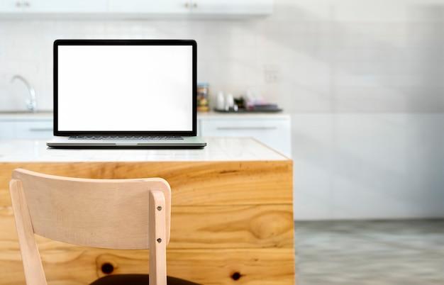 Computer portatile dello schermo in bianco del modello sulla tavola di legno nella stanza della cucina