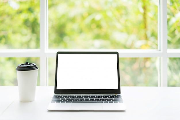Computer portatile dello schermo in bianco e tazza di caffè sulla tabella al caffè del caffè con la natura nella priorità bassa.