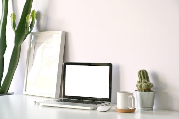 Computer portatile dello schermo in bianco nello studio del sottotetto.