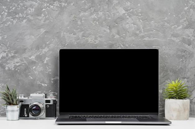 Computer portatile di vista frontale con piante e macchina fotografica