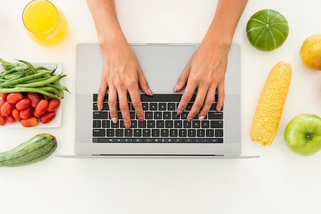 Computer portatile di vista superiore circondato da frutta