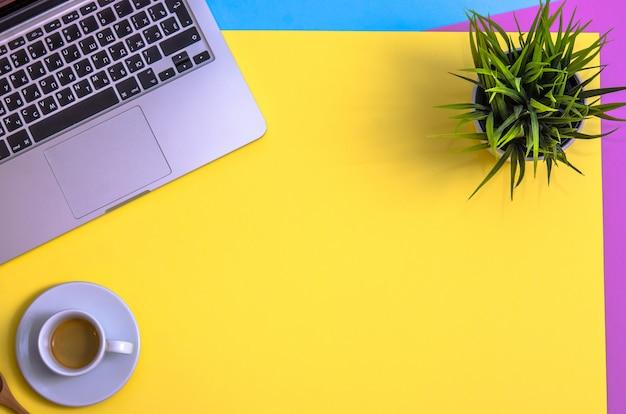 Computer portatile e appunti con caffè e pianta su sfondo giallo, blu e porpora