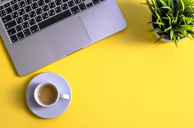 Computer portatile e appunti con caffè e pianta su sfondo giallo. distesi. vista dall'alto. copia