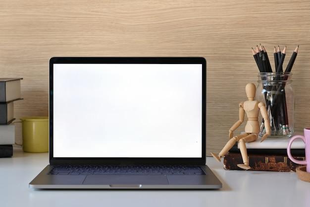 Computer portatile e articoli per ufficio dello schermo in bianco del modello sulla tavola bianca.
