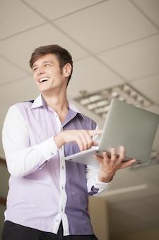 Computer portatile e battitura a macchina sorridenti della tenuta del giovane