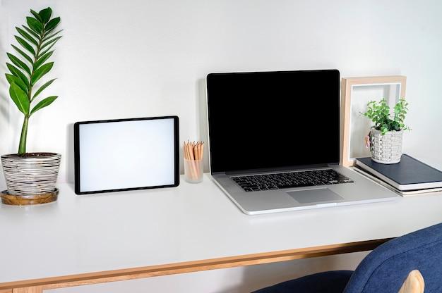 Computer portatile e compressa del modello con lo schermo in bianco sul tavolo superiore bianco.
