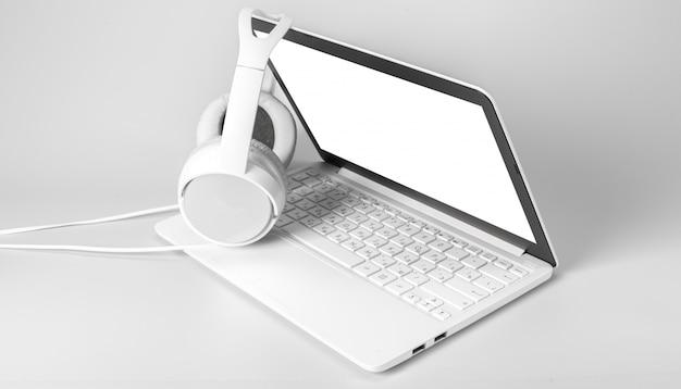 Computer portatile e cuffia isolati su bianco