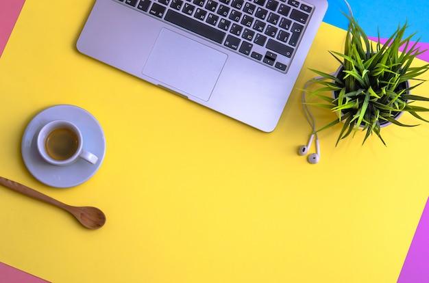 Computer portatile e cuffie con caffè e pianta su sfondo giallo, blu e porpora