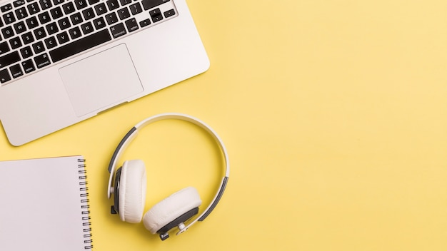 Computer portatile e cuffie su fondo giallo