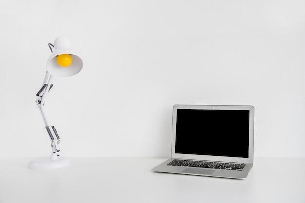 Computer portatile e lampada da tavolo su sfondo bianco