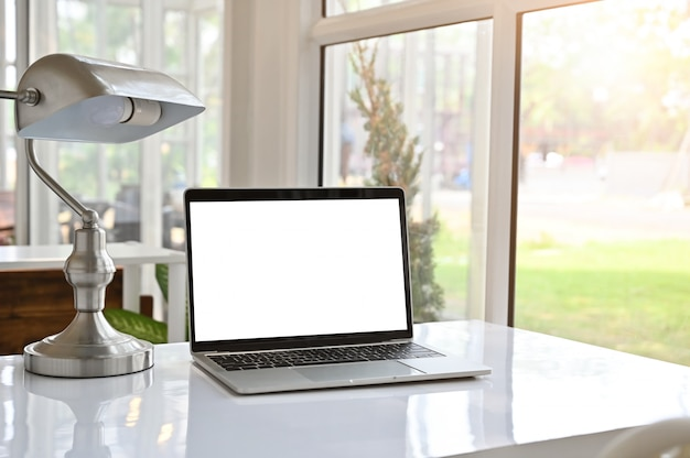 Computer portatile e lampada del modello sul tavolo.
