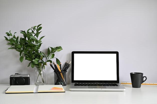 Computer portatile e macchina fotografica del computer dell'area di lavoro con carta del taccuino con caffè.
