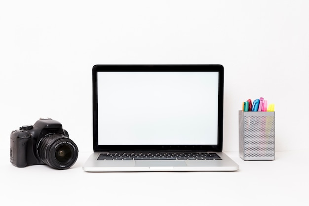 Computer portatile e macchina fotografica moderni su fondo bianco