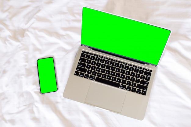 Computer portatile e smart phone dello schermo verde in bianco di vista superiore,