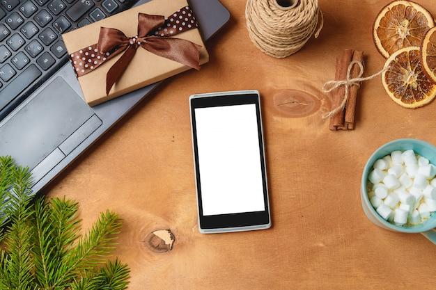 Computer portatile e telefono con lo schermo vuoto per la composizione stagionale in natale