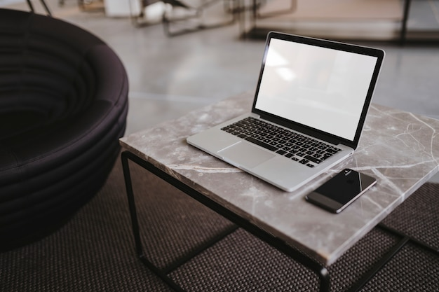 Computer portatile e un telefono su un tavolo di marmo