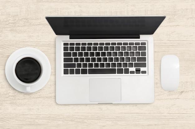 Computer portatile e una tazza di caffè sulla tavola di legno.
