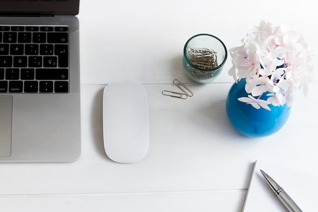 Computer portatile e vaso blu con fiori rosa sulla scrivania sul posto di lavoro
