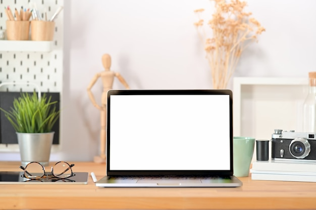 Computer portatile elegante dello schermo in bianco dello scrittorio del posto di lavoro, macchina fotografica d'annata, manifesto e aggeggio