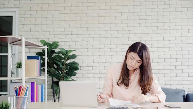 Computer portatile funzionante della bella giovane donna asiatica sorridente sullo scrittorio in salone a casa.