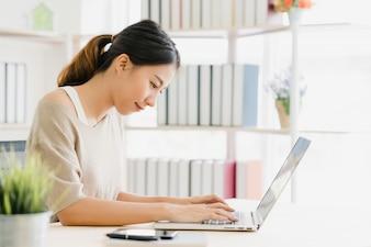 Computer portatile funzionante della bella giovane donna asiatica sorridente sullo scrittorio in salone a casa