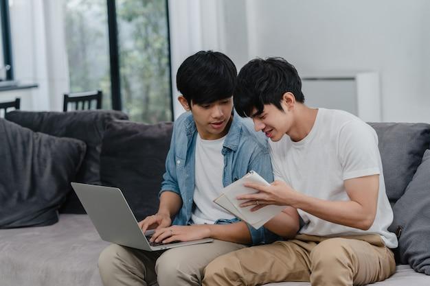 Computer portatile funzionante delle giovani coppie gay asiatiche a casa moderna. l'asia lgbtq + gli uomini si rilassano felici usando il computer e analizzando insieme le loro finanze in internet mentre si trovano il divano nel soggiorno di casa.