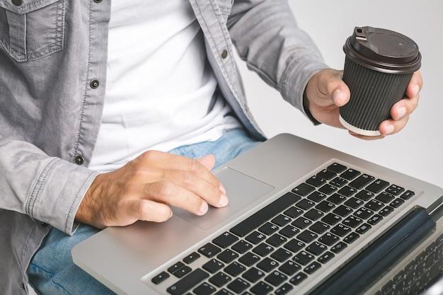 Computer portatile funzionante rilassato dell'uomo di affari casuali. avvicinamento.