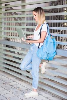Computer portatile grazioso di lettura femminile vicino alla parete