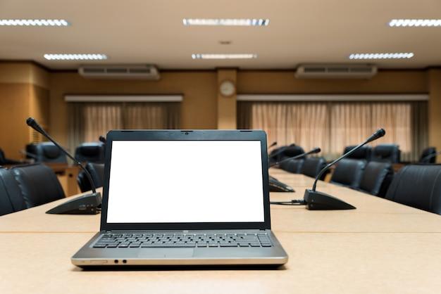Computer portatile in bianco bianco disposto sul tavolo di riunione di legno nella sala riunioni vuota.