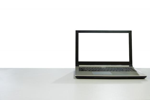 Computer portatile in bianco dell'esposizione sullo scrittorio bianco con il fondo dello spazio della copia