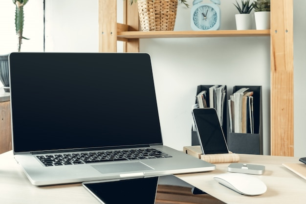 Computer portatile in una stanza leggera sul tavolo di lavoro con articoli per ufficio