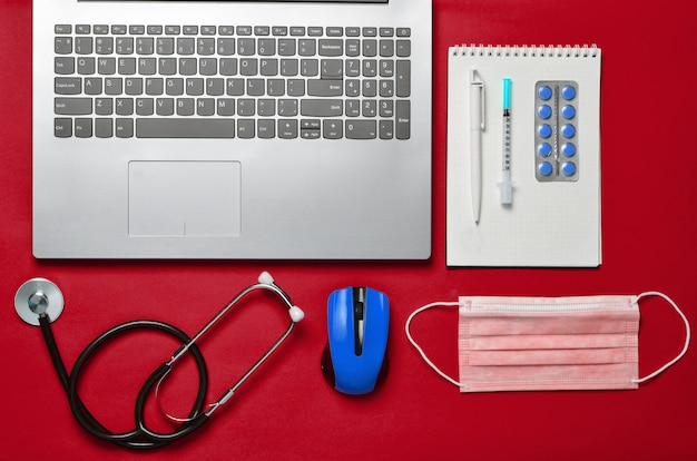 Computer portatile, mouse senza fili, taccuino, stetoscopio, pillole su fondo rosso