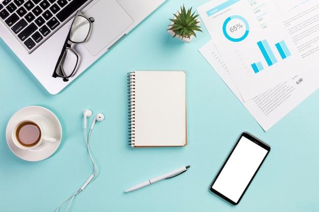 Computer portatile, occhiali da vista, tazza di caffè, auricolari, blocco note a spirale, penna, telefono cellulare e grafico del budget sulla scrivania
