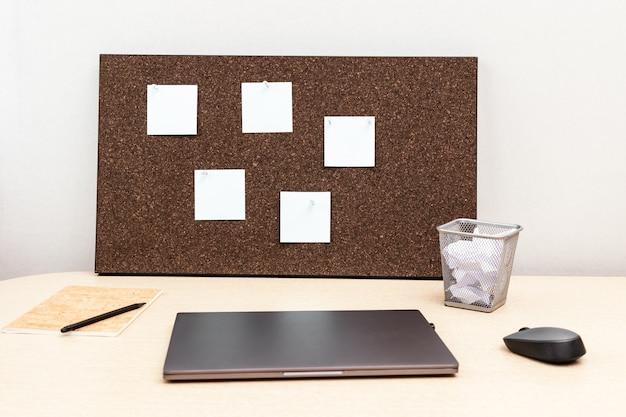 Computer portatile per lavoro e bacheca in legno con note appiccicose vuote
